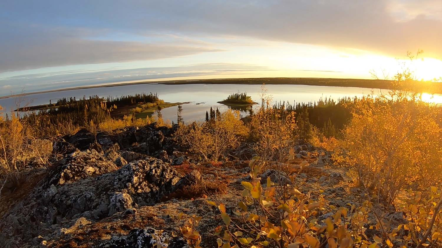 Landscape image with fall colored grass surrounding water and the sun setting on the horizon