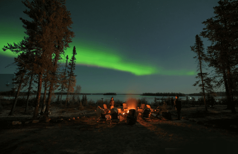 Watching the Northern Lights while sitting around a camp fire