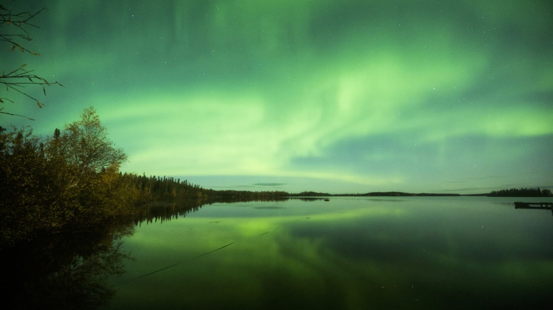 Image of green skies from the Northern Lights reflecting in the lake