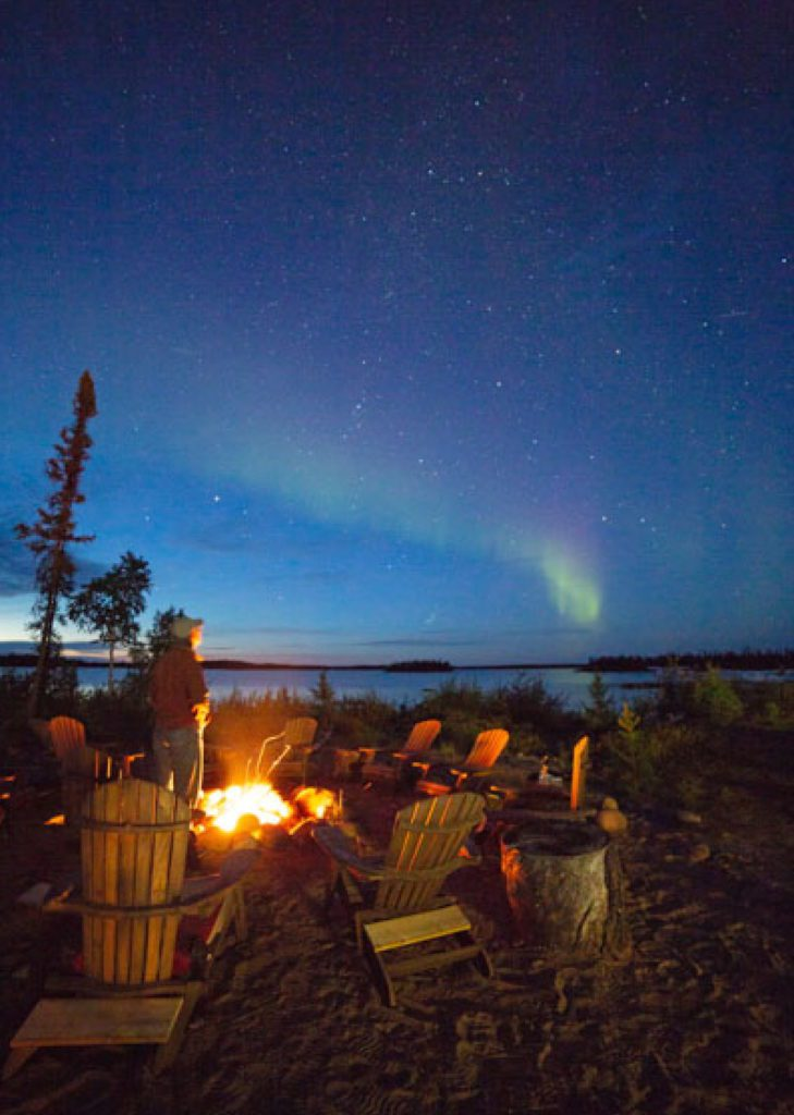 Someone standing by a campfire surrounded by wooden lounging chairs while waiting the Northern Lights in the background