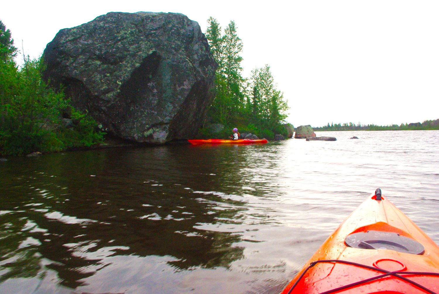 Two people kayaking next to the Andrea Erratic